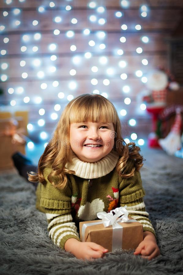 Beautiful cute little girl on christmas background with gift stock image