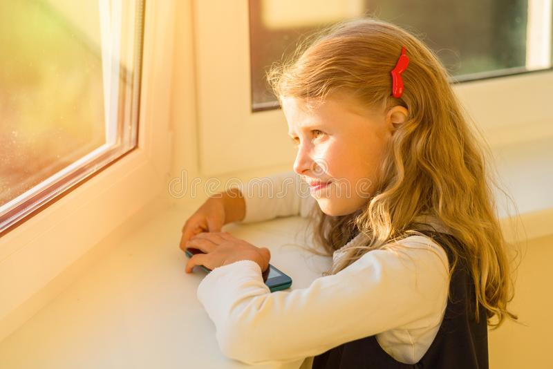 Beautiful cute little girl dressed in school uniform looking out royalty free stock photography