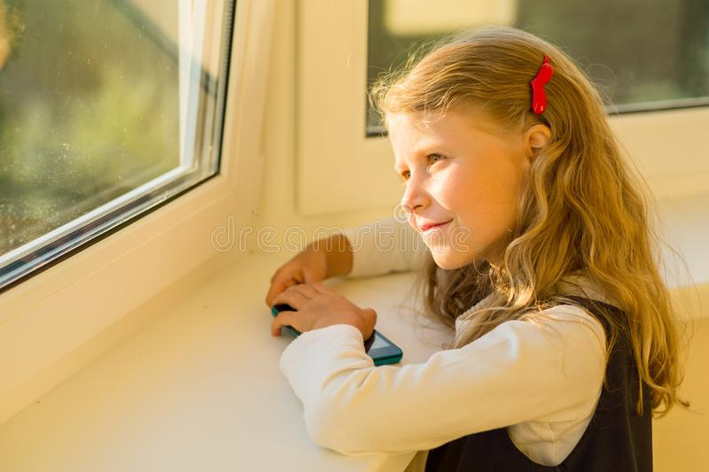 Beautiful cute little girl dressed in school uniform looking out the window stock images
