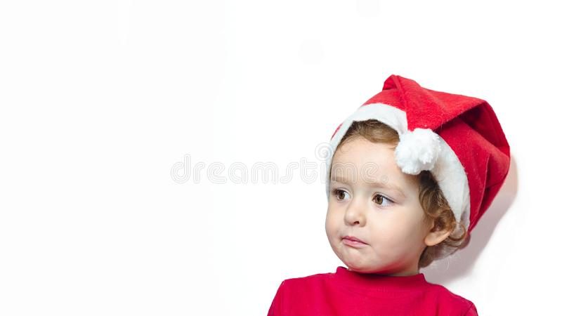 Beautiful cute little girl in red clothes, santa claus hat on white background with copy space. baby dreams of holiday, gifts. royalty free stock photo