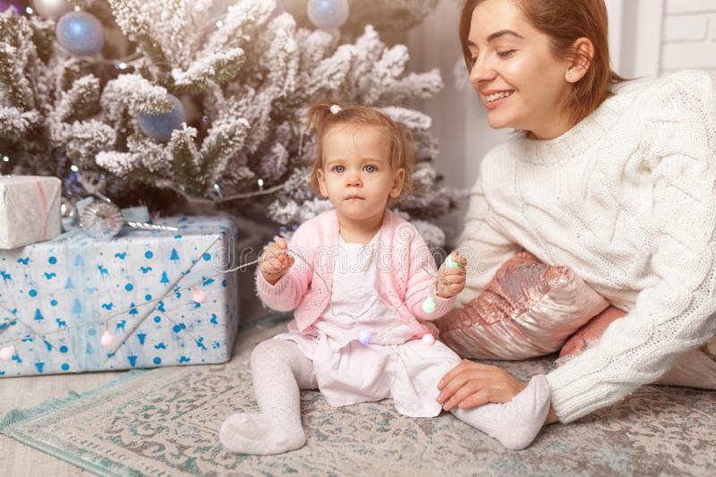Beautiful cute little girl sitting on the floor near the New Year tree next to her mother. royalty free stock images