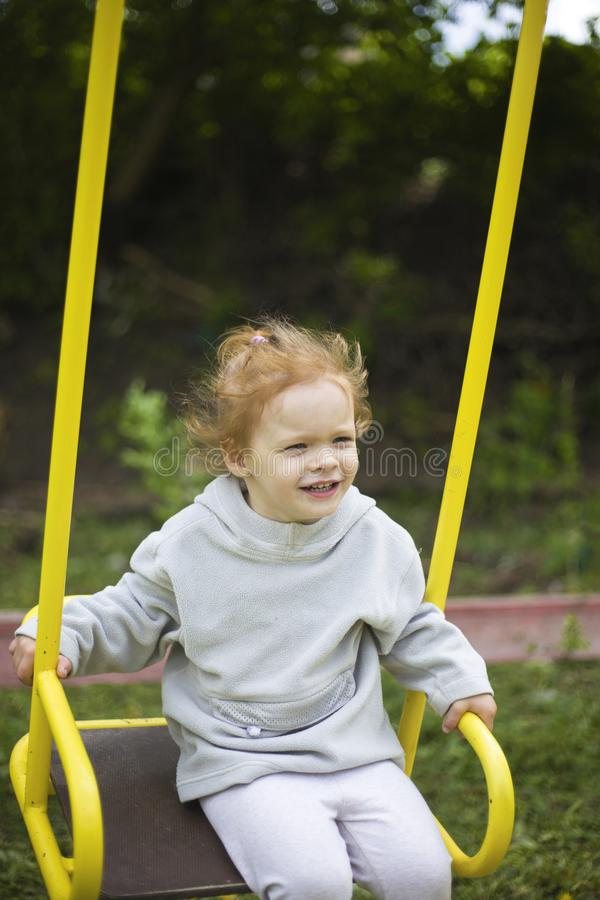 Beautiful little redhead girl riding a swing on the playground royalty free stock photo