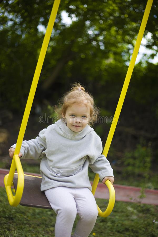 Beautiful little redhead girl riding a swing on the playground stock images