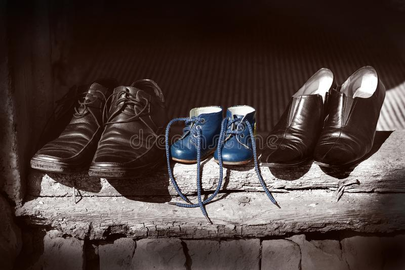 Beautiful cute nice shoes family Father mother shoes boots and baby child blue color old fashion shoes standing on old worn wood stock photography