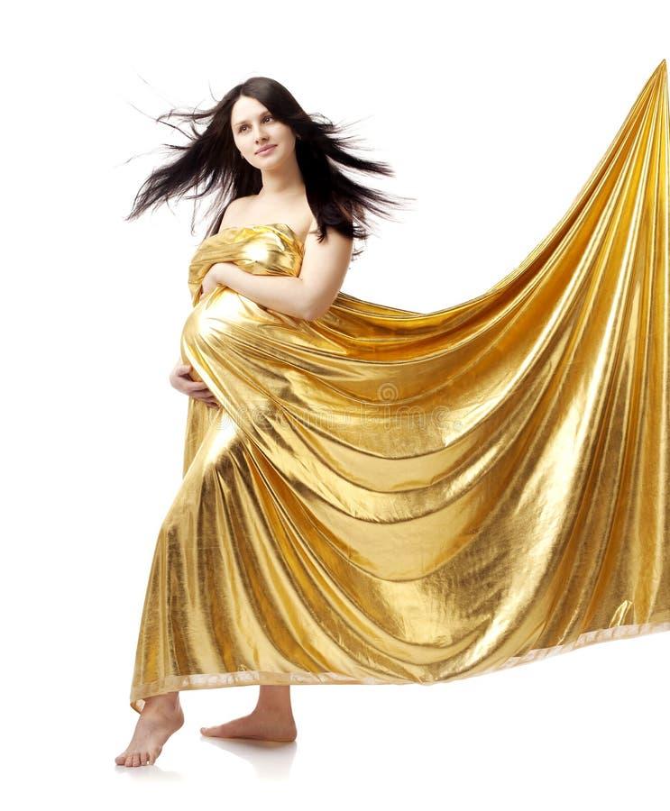 Beautiful cute pregnant girl in gold stock image