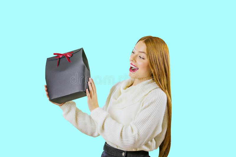A beautiful cute red-haired girl in a white blouse holds a black gift box with a green velvet ribbon, picks up a gift royalty free stock image