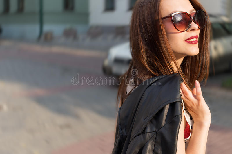 Beautiful cute happy smiling brunette girl in the big sunglasses walking around the city at sunset stock photography