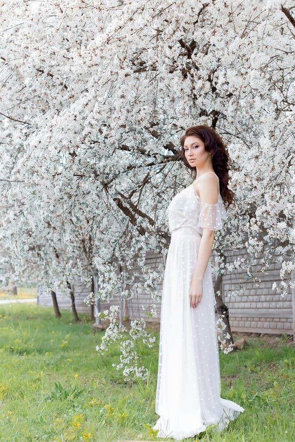 Beautiful cute sweet girl bride with gentle eye make-up full lips in white light dress walks in the lush garden on warm s. Beautiful cute sweet girl bride with stock photo