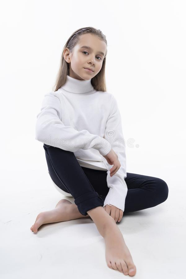 Beautiful cute teen girl wearing a white turtleneck sweater and jeans sits on the floor. Isolated on white background. Advertising royalty free stock images