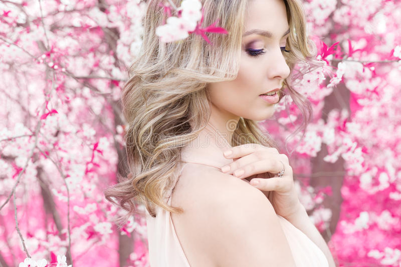 Beautiful cute tender young blonde girl in the rose garden in flowering trees in the gentle fabulous colours stock image