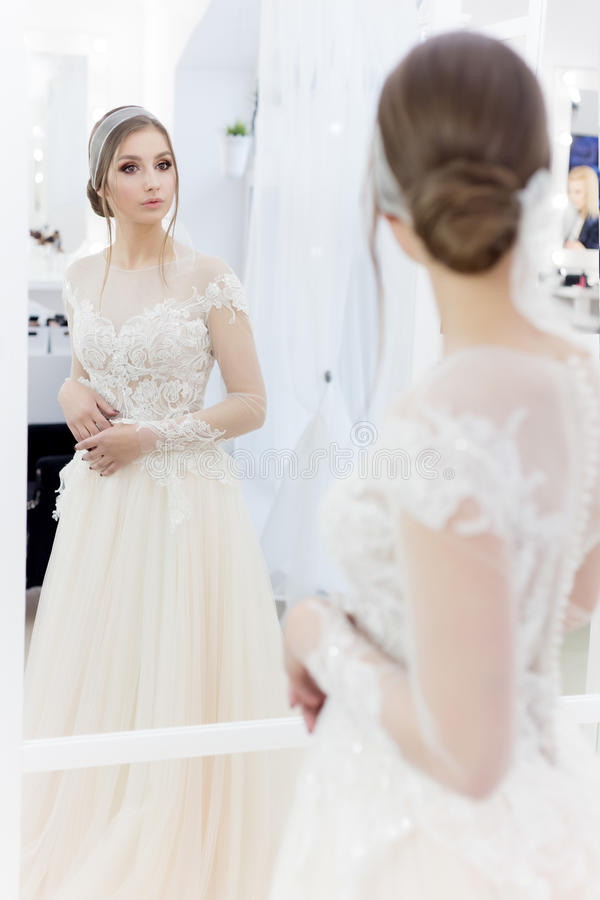 Beautiful cute tender young girl bride in wedding dress in mirrors with evening hair and gentle light make-up stock photos