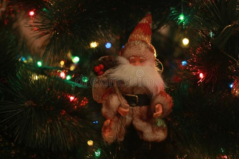 Beautiful cute toy Santa Claus with gifts on the Christmas tree with colorful garlands. Festive decorations. Toy Santa Claus royalty free stock photo