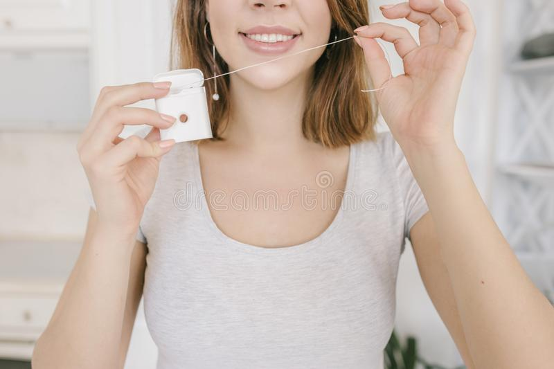 Beautiful cute woman is smiling with dental floss. Dental health care clinic. stock photos