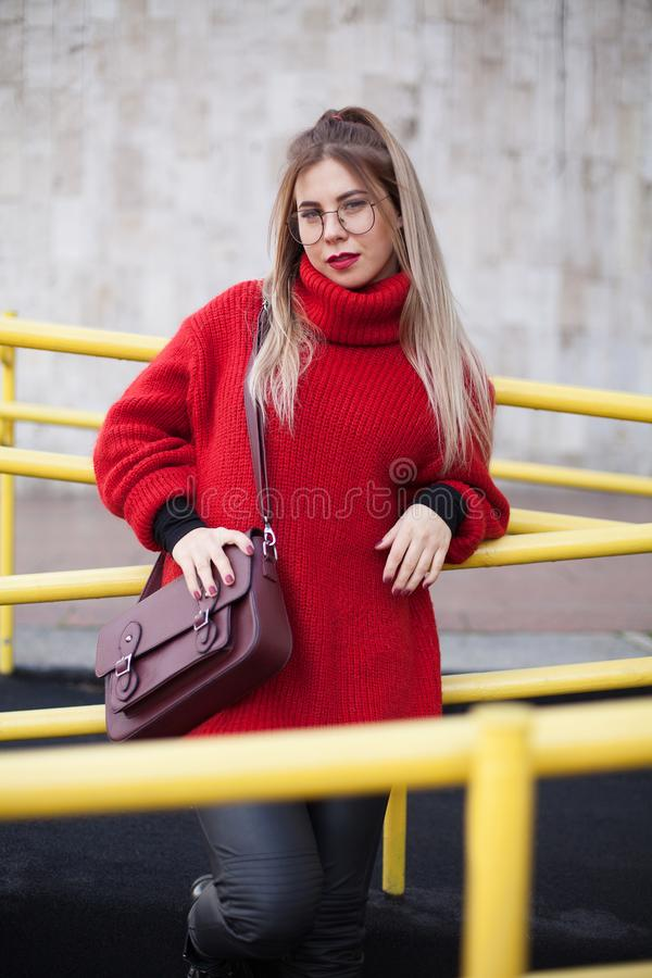 Beautiful cute young European hipster teen girl, on a background of marble wall and yellow handrails royalty free stock images