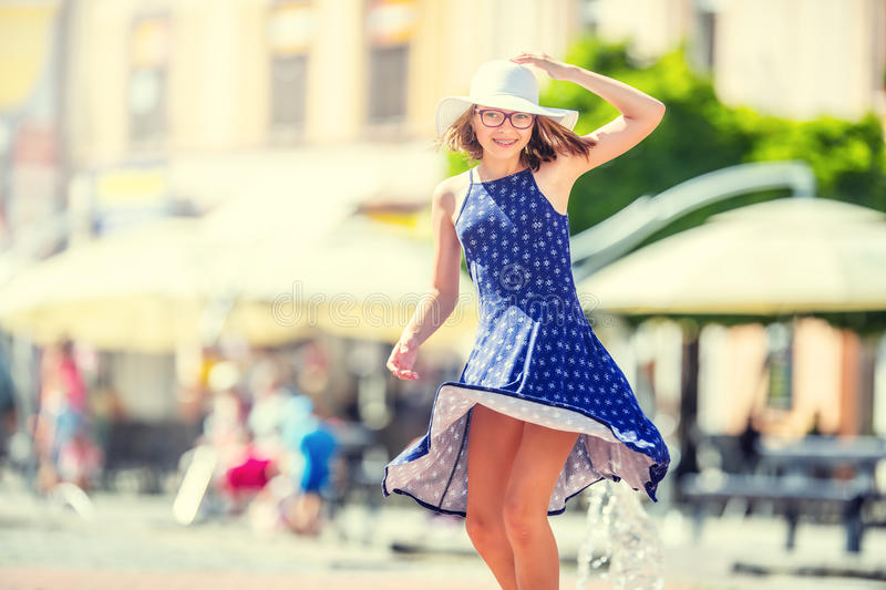 Beautiful cute young girl dancing on the street from happiness.Cute happy girl in summer clothes dancing in the sun royalty free stock photography