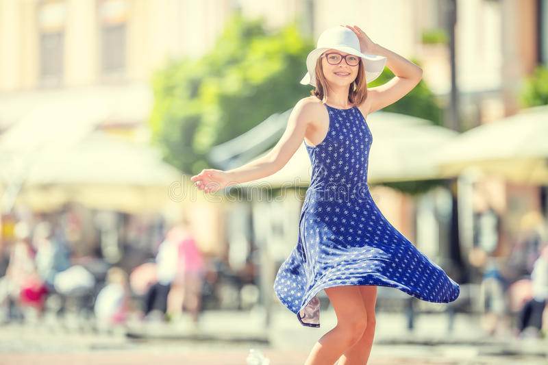 Beautiful cute young girl dancing on the street from happiness.Cute happy girl in summer clothes dancing in the sun stock photography
