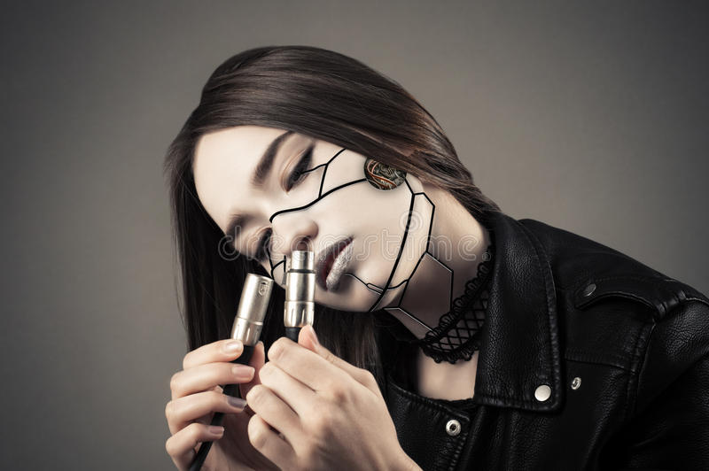 Beautiful cyberpunk girl looking on two electric cables royalty free stock photography