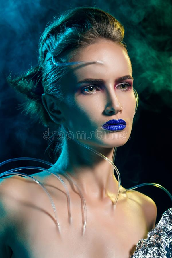 Beautiful cyborg girl with the hoses stick out her skin. Beautiful cyborg girl wearing in a foil clothes with the hoses stick out her skin. Theatrical smoke and stock photography