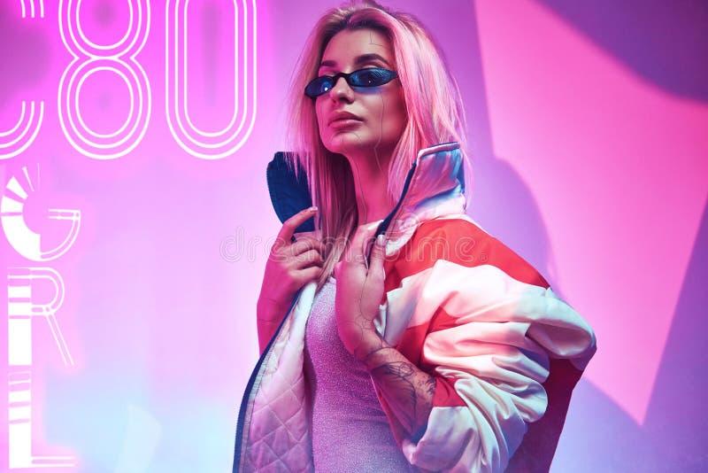 Cyborg woman wearing modern clothes in futuristic nightclub. Cyberpunk concept art. Beautiful cyborg woman wearing modern clothes in futuristic nightclub royalty free stock images