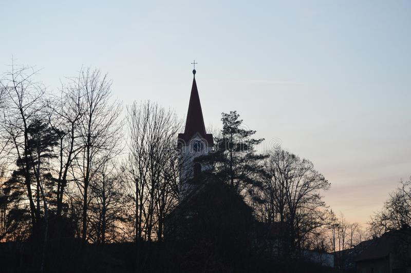 Church behind forest after sunset royalty free stock photo