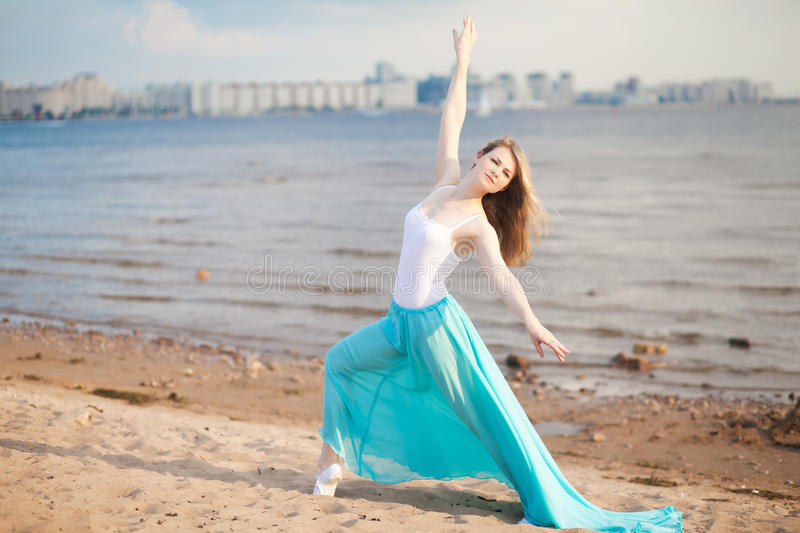 Beautiful dancer poses on the beach stock photo