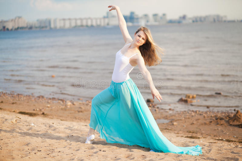Beautiful dancer poses on the beach stock images