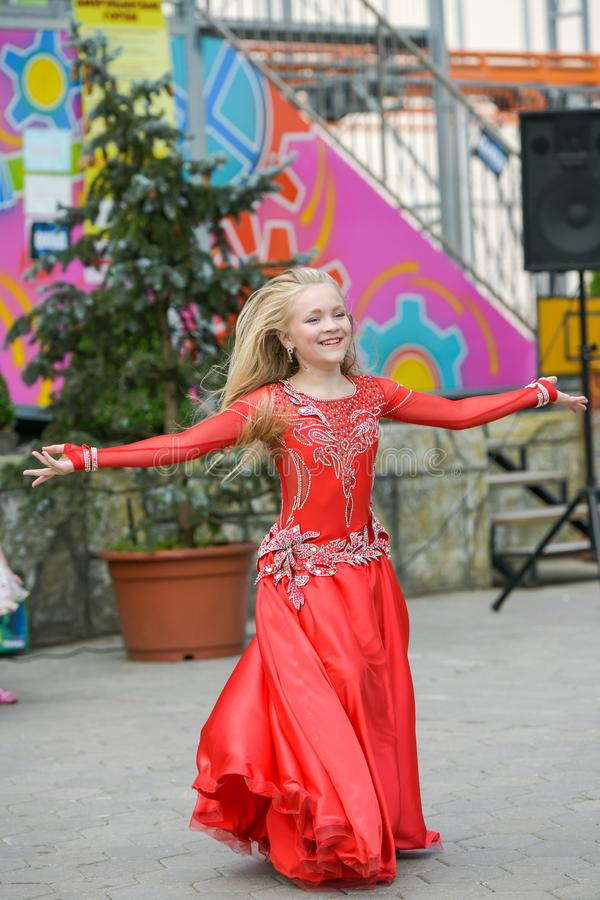 Beautiful dancer in a red dress. Beautiful young girl dancing in a red dress. Dance in public. Talented kid does dancing royalty free stock photography