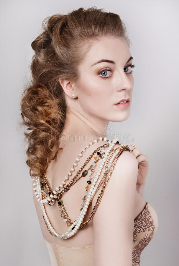 Beautiful dark blonde woman in a gold and pearls necklace. Portrait of a young beautiful dark blonde woman in a gold and pearls necklace. She wears satin beige stock photo