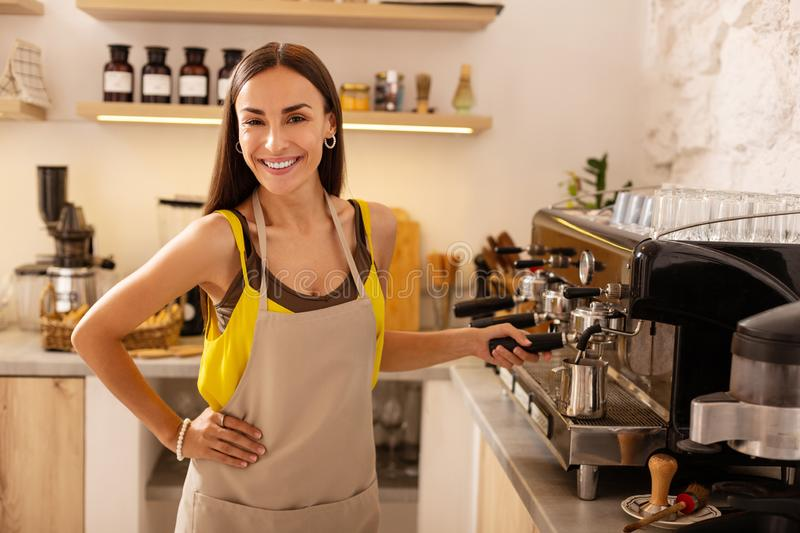 Beautiful dark-eyed woman making coffee for clients stock images