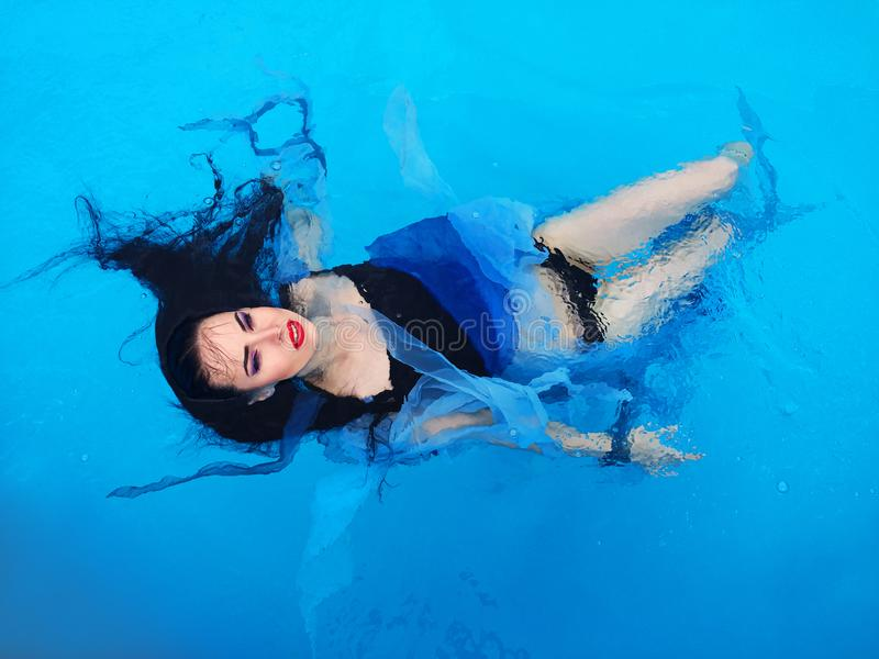 Beautiful dark hair woman on the water in the swimming pool. Beautiful dark hair woman in dress laying down on the water in the swimming pool stock images