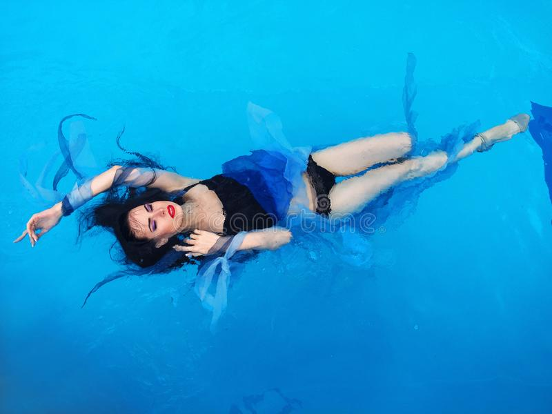 Beautiful dark hair woman on the water in the swimming pool. Beautiful dark hair woman in dress laying down on the water in the swimming pool royalty free stock photos