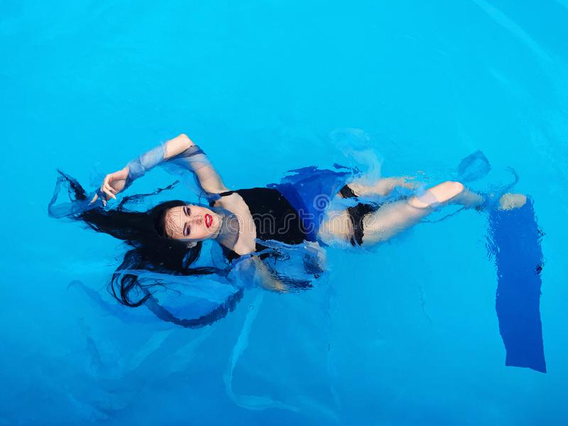 Beautiful dark hair woman on the water in the swimming pool. Beautiful dark hair woman in dress laying down on the water in the swimming pool royalty free stock image