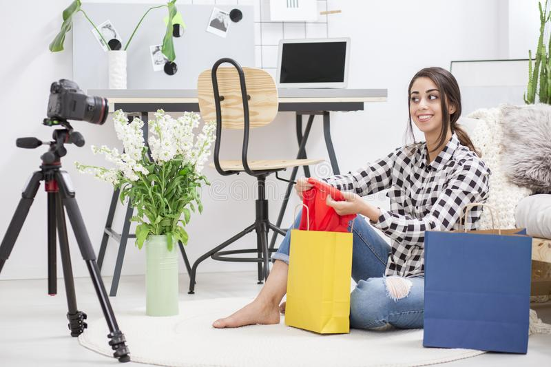 Female showing new clothes. Beautiful dark haired female showing her new clothes on video blog royalty free stock images