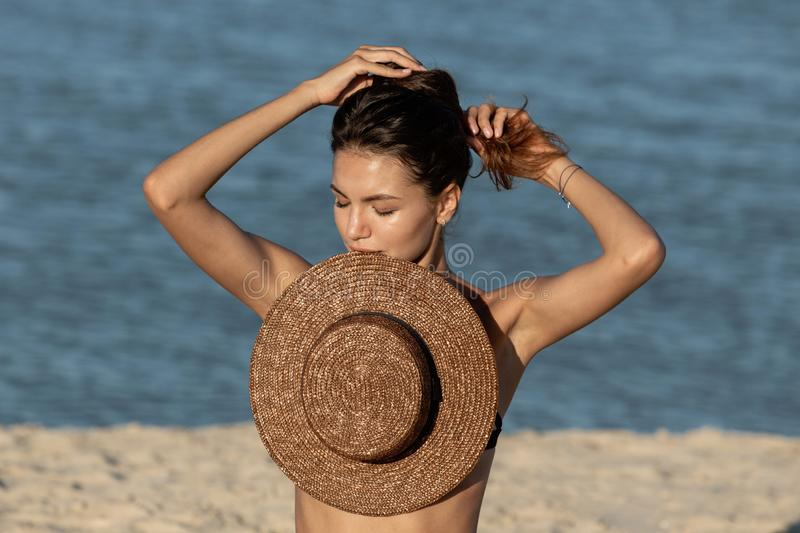 Beautiful dark-haired girl in swimsuit and jean shorts sit on the sand near the sea and hold a hat in her teeth on a royalty free stock image