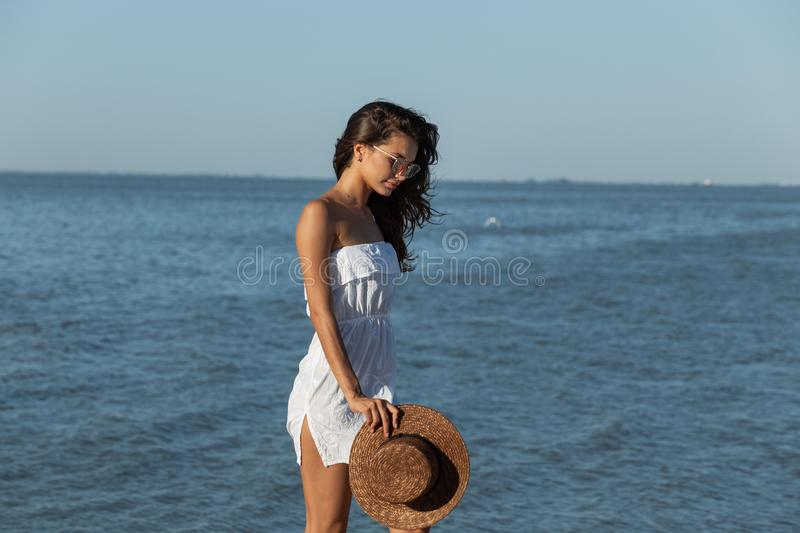 Beautiful dark-haired girl in white dress and sunglasses hold hat in hand and walk near the sea on a sunny day.  royalty free stock photography