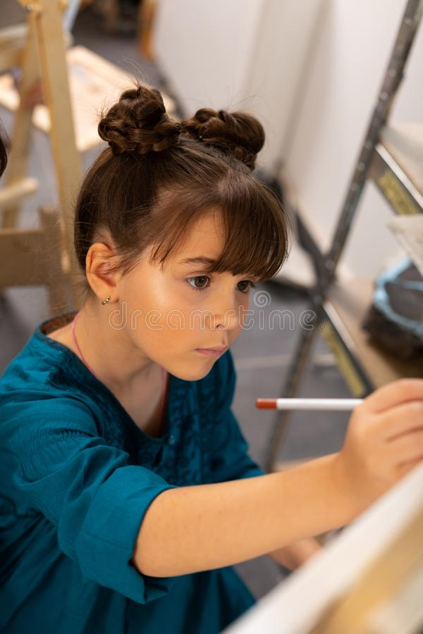 Beautiful dark-haired schoolgirl feeling involved in painting royalty free stock image