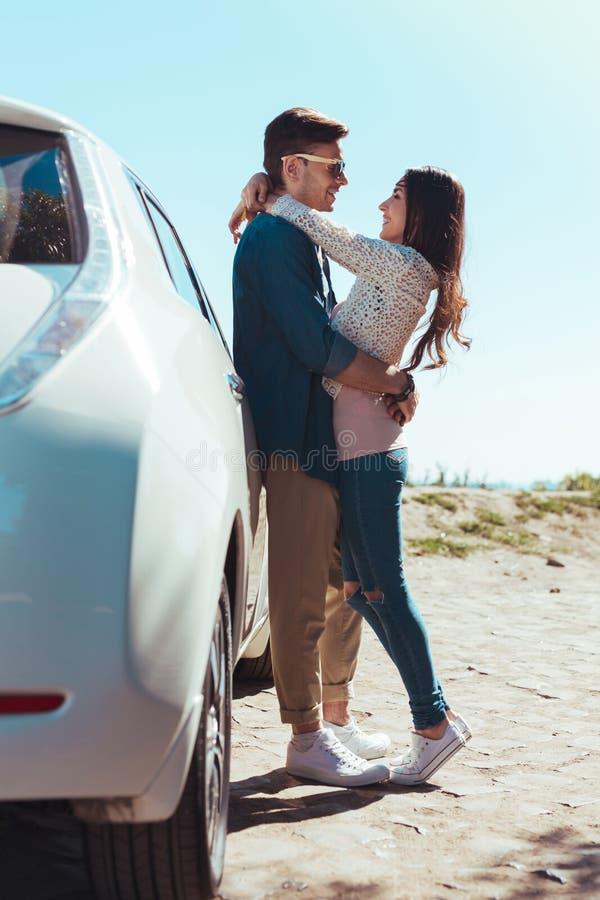 Beautiful dark-haired woman hugging her man standing near car. Hugging man. Beautiful dark-haired women wearing jeans feeling lovely while hugging her men stock image