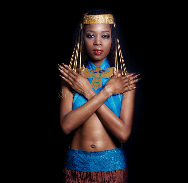 Beautiful dark-skinned girl black woman in the image of the Egyptian queen with red lips bright makeup demonstrates long nails royalty free stock images