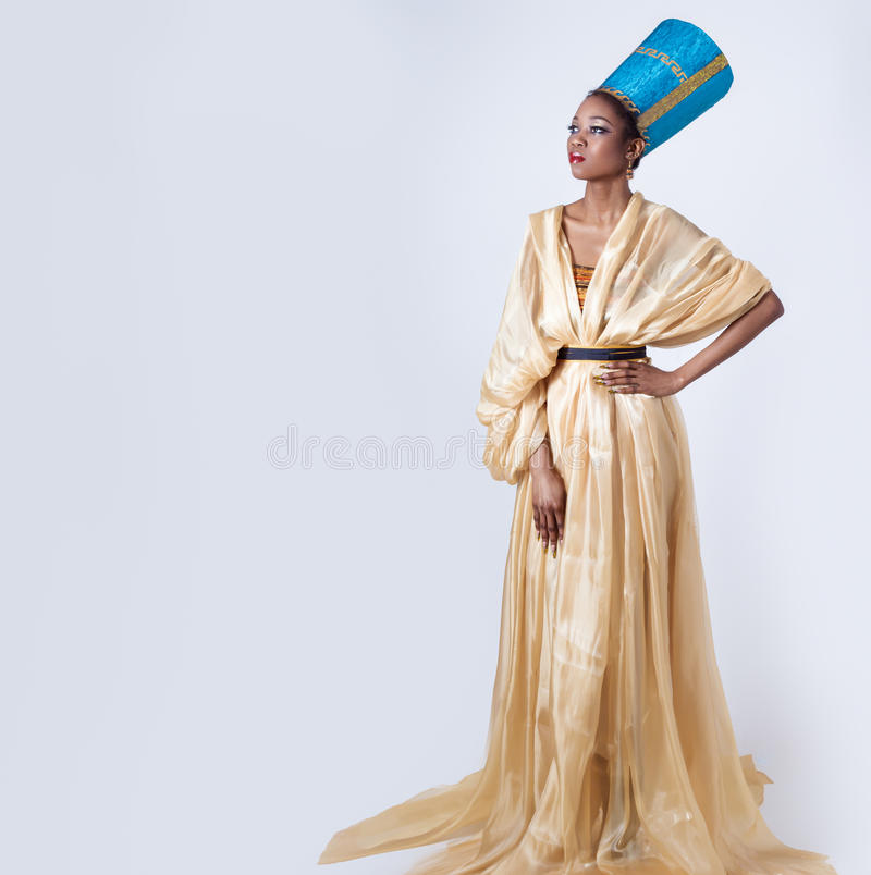 Beautiful dark-skinned girl black woman in the image of the Egyptian queen with red lips bright makeup demonstrates long nails stock photos