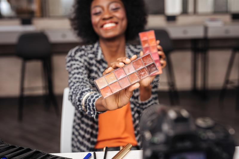 Beautiful dark-skinned model with curly hair demonstrating new color palette stock photo