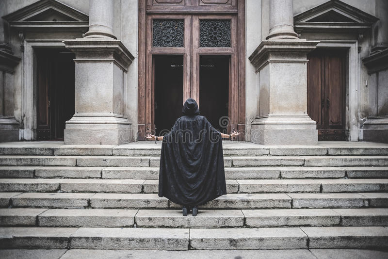 Beautiful dark vampire woman with black mantle and hood royalty free stock image