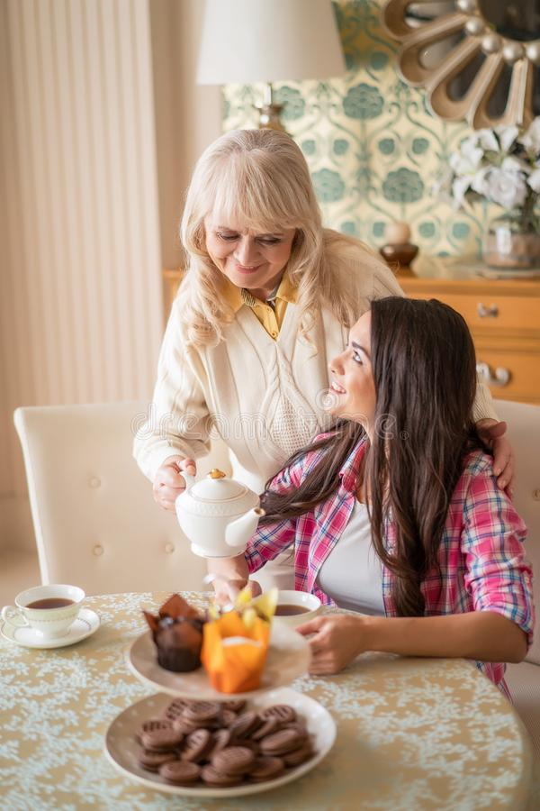 Senior female pouring tea from teapot into her daughter`s cup. Beautiful Daughter Looks At Her Caring Mother, Who Carefully Pours The Tea From Ceramic Teapot stock image