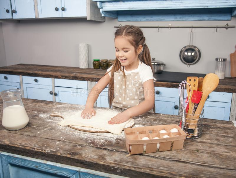 A beautiful daughter rolls out a dough for baking cookies while her mom relaxes stock photo