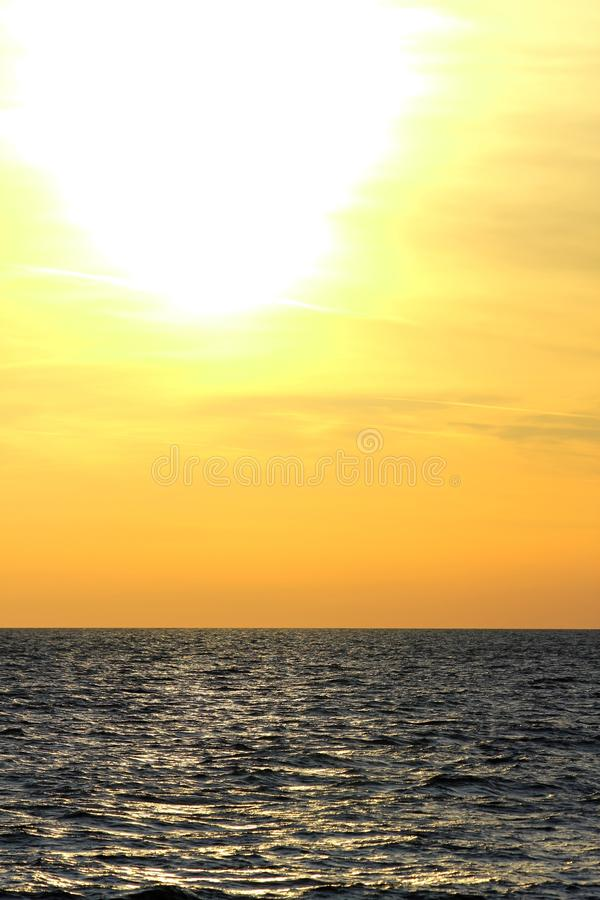 Beautiful dawn - perfect sunset horizon over ocean water - vertical shot. Beautiful sunset on the sea in the high grass - sunset light, horizontal, blurred sea stock images