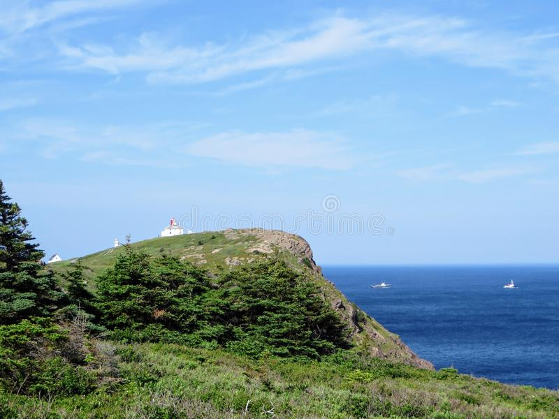 Beautiful day along the coast of Newfoundland viewing the lighthouse on Cape Spear. Boats passing by along the open ocean. stock images