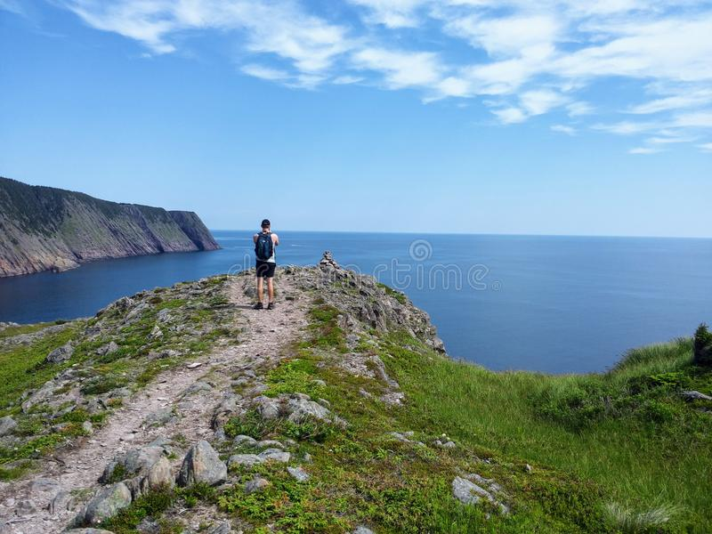 Beautiful day along the coast of Newfoundland viewing the open ocean along the sugarloaf trail. Man taking a photo on his camera of the open and calm atlantic stock photo