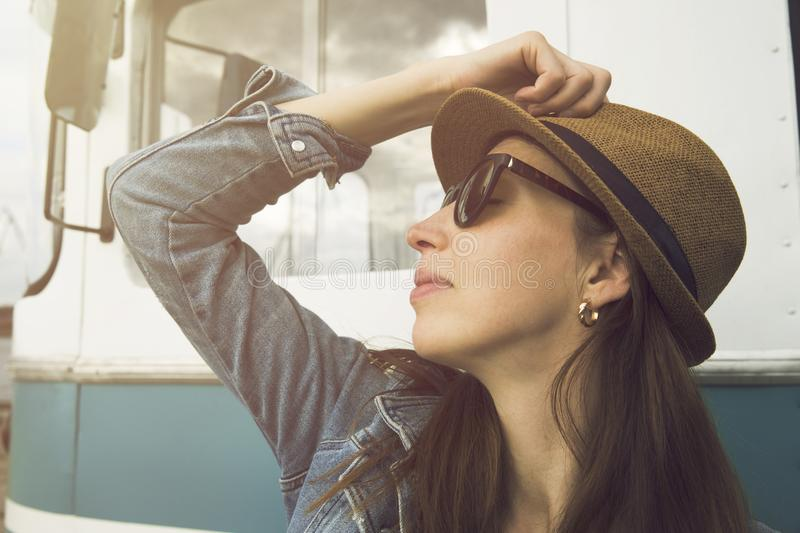 Beautiful day. Attractive young woman in hat standing by the travel van. Car travel, summer vacation and adventure royalty free stock photos