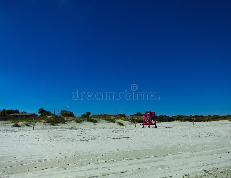 A red lifeguard chair. On a beautiful day the beach was deserted. We see several color contrasts. Photo taken on trip to Daytona Beach, Florida, U.S.A .; January royalty free stock images