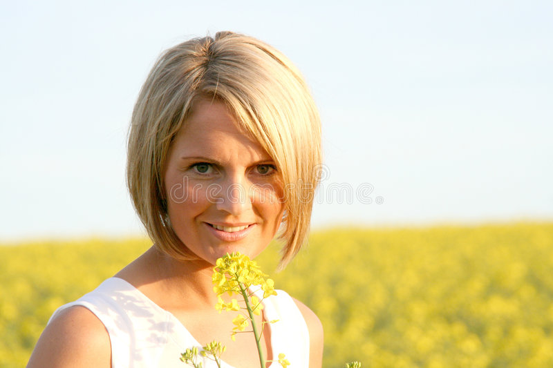 Beautiful Day - Summer time. A beautiful young woman and yellow flowers royalty free stock images