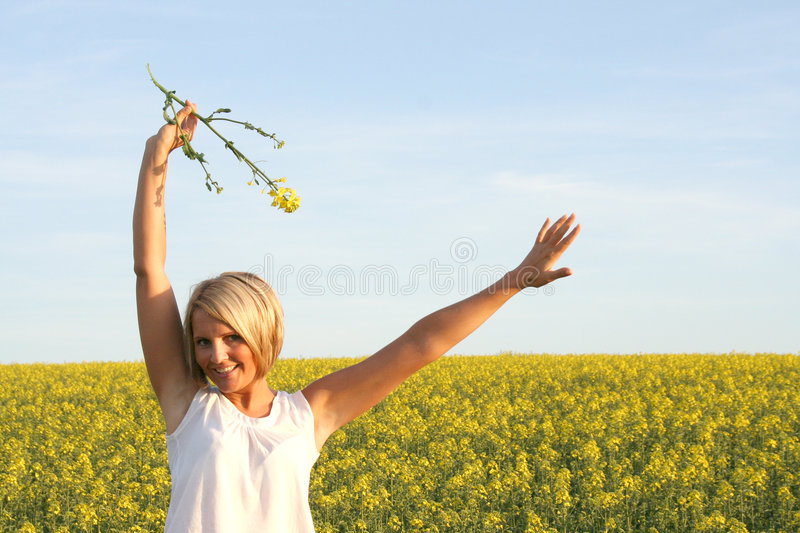 Beautiful Day - Summer time. A beautiful young woman and yellow flowers stock photography